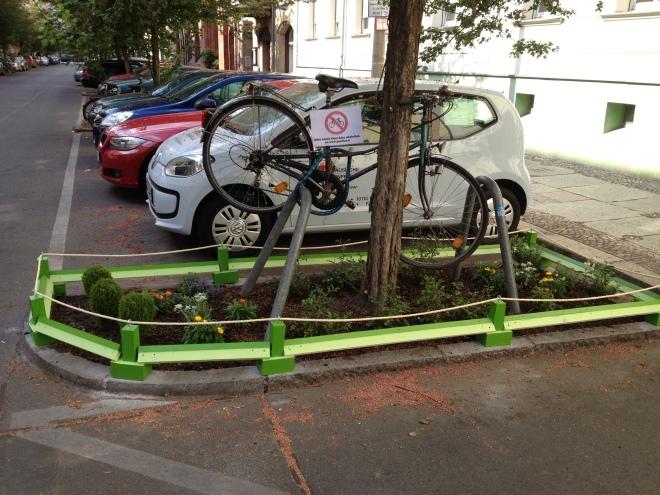 Baumscheibe mit Fahrrad, das an dem Baum befestigt istm